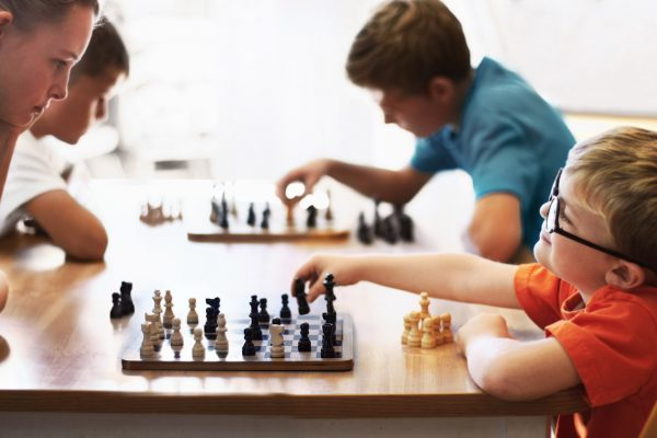 Young boy wearing spectacles and playing chess with an older child