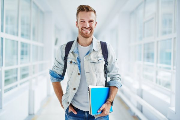Happy guy with book and touchpad looking at camera