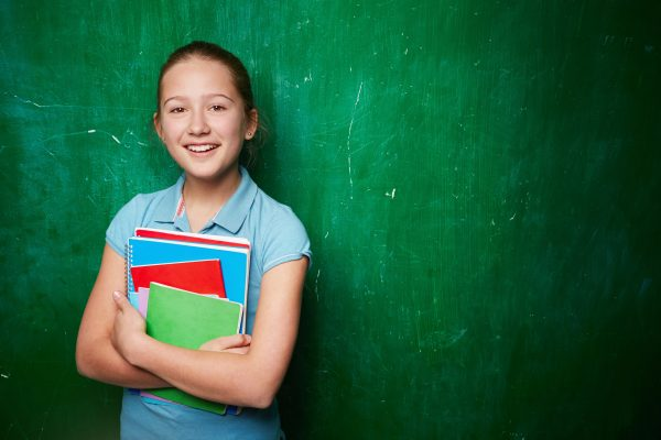 Portrait of cute schoolgirl with textbooks looking at camera by the blackboard