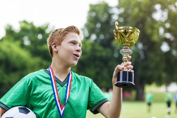 Teenage male soccer athlete admires his team's trophy. The trophy is a golden cup. He is wearing a medal around his neck and holding a soccer ball. He has red hair and is wearing a green jersey.